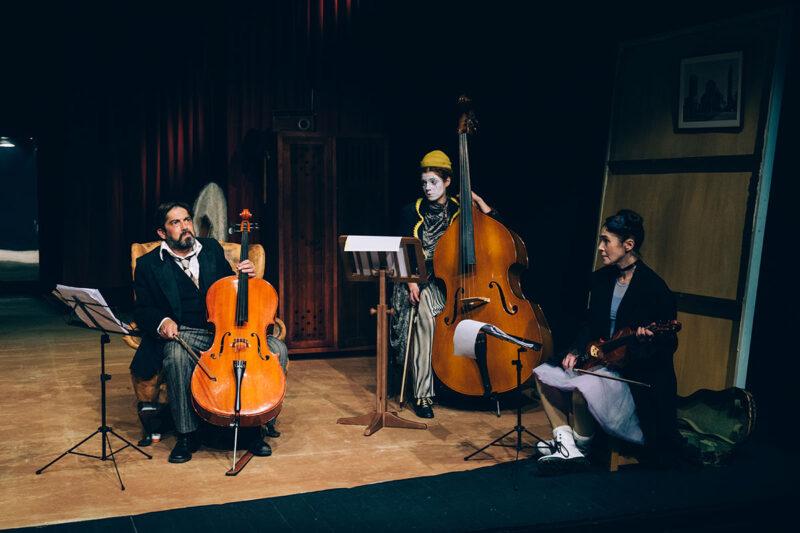 Plano geral da cena onde estão três personagens com os seus instrumentos e partituras.
